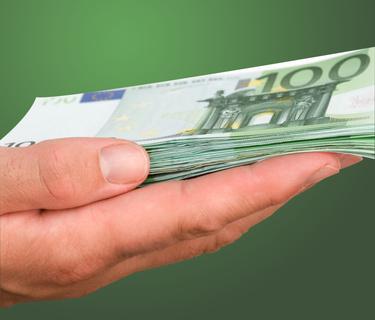Ausgestreckte Hand hält einen Stapel 100-Euro Noten