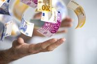 Eine Hand wirft viele Euro-Scheine in die Luft