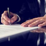 Ein Mann im Anzug unterzeichnet einen Vertrag