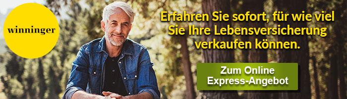 Ein lächelnder Mann mit Jeanshemd sitzt vor einem Waldrand